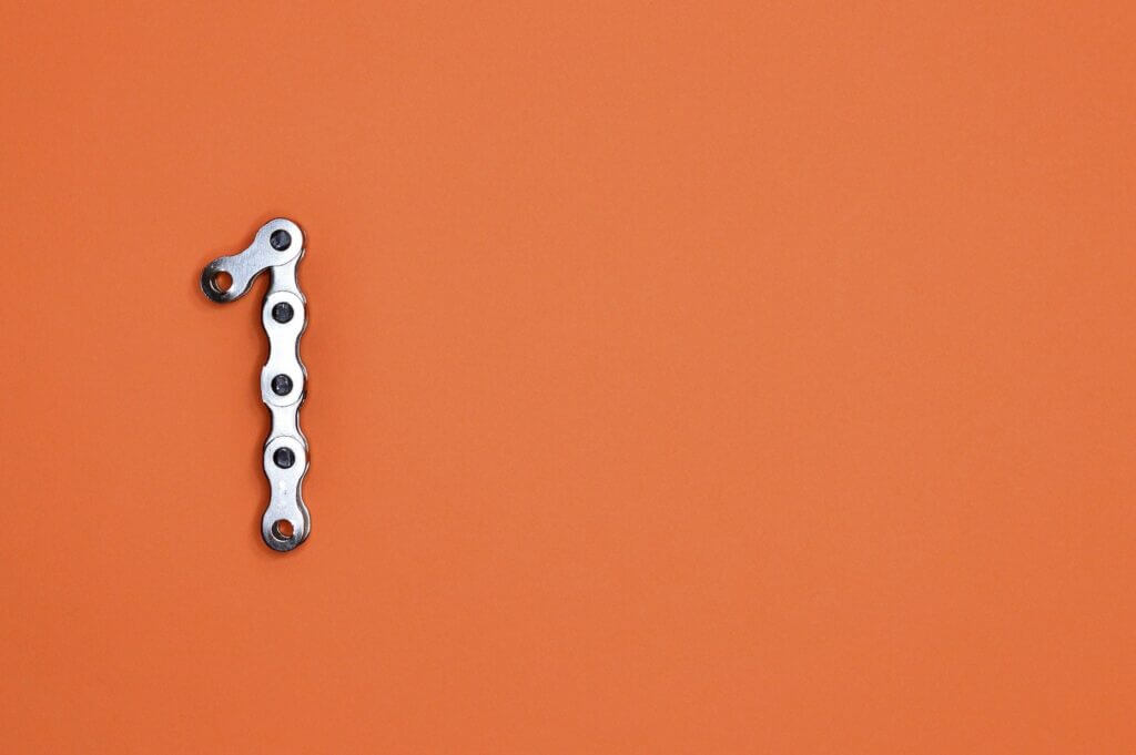 Bright orange background silver bike chain forms number one on left side of image