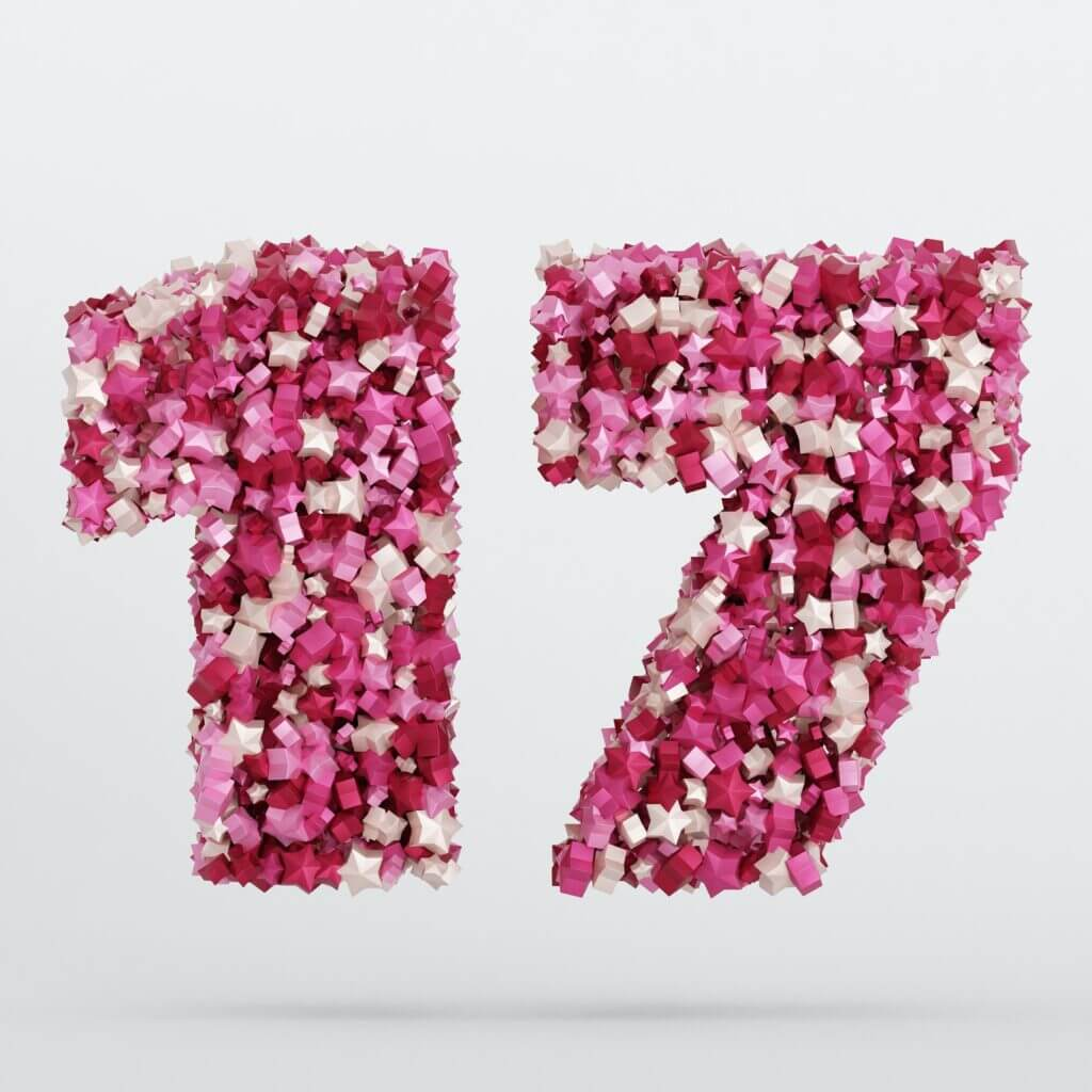 Hundreds of small pink, white, and red origami stars come together to form a 3 dimensional number 17