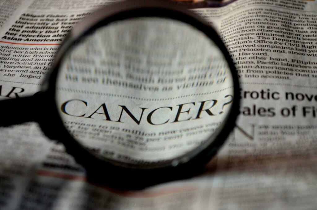 Magnifying glass in foreground held over newspaper the word Cancer is enlarged in magnifying glass