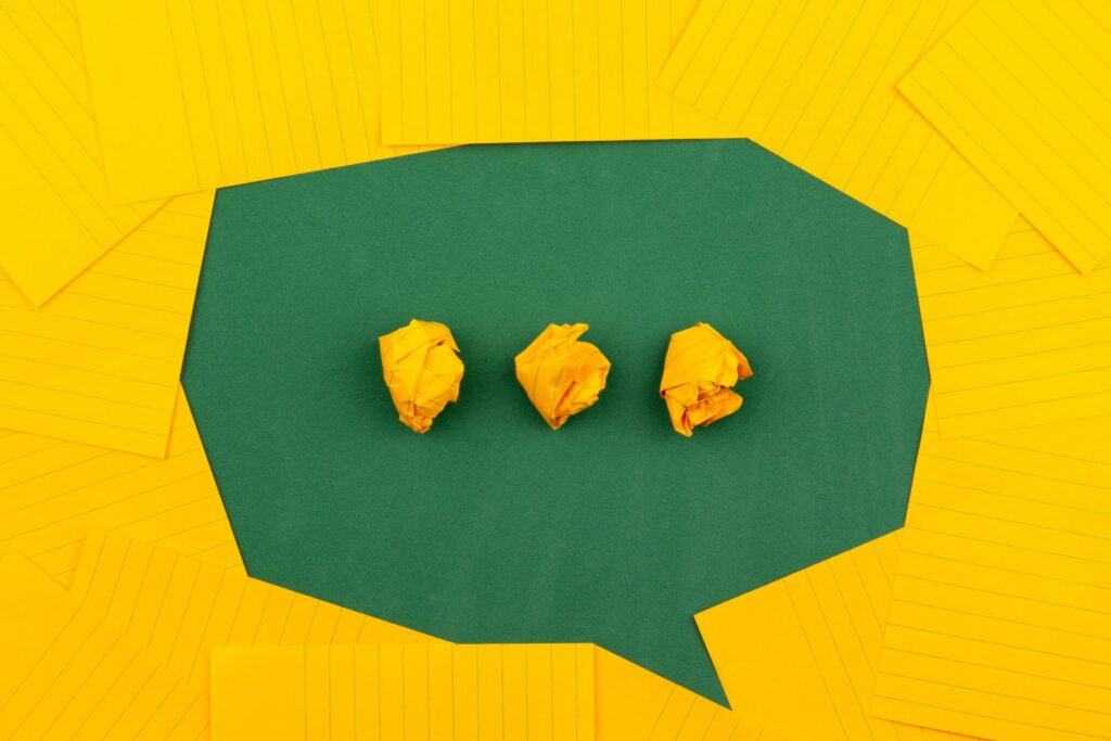 Yellow note cards laid all angles on top of green background creates the outline of a speech bubble