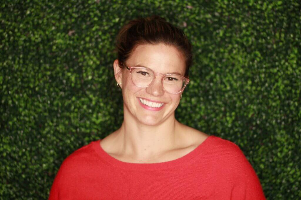 Shoulder up picture of Laura in red shirt pink glasses her hair is up she sits in front of greenery