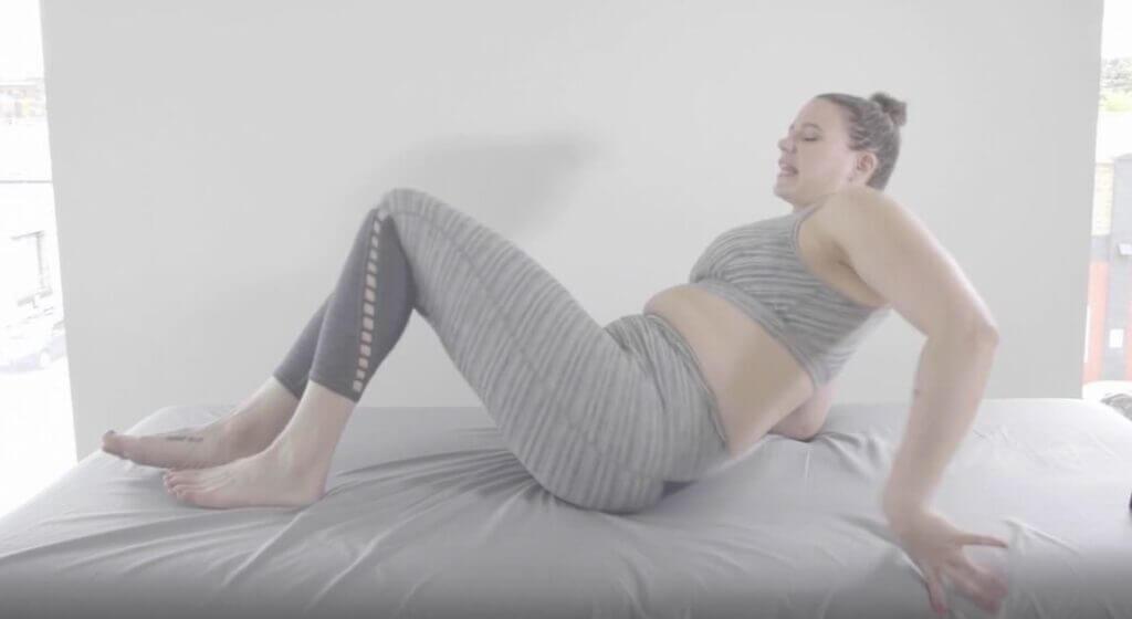 Beginning to recline bottom on floor hands behind her shoulders elbows bend feet on floor knees up