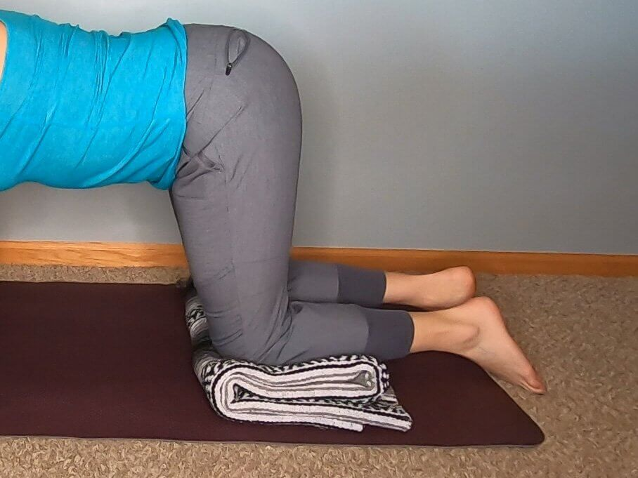 On hands and knees with a blanket folded over to stack to raise height and reduce flexion of ankles