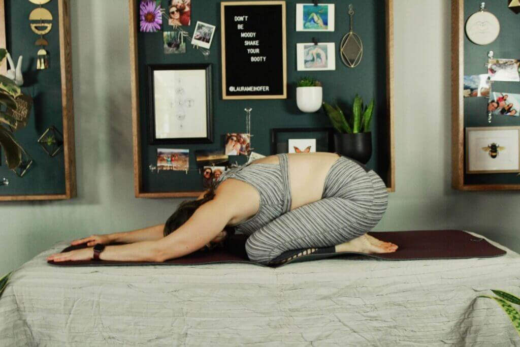 Laura on knees feet under buttocks bent forward face rests on floor arms above head rest on surface