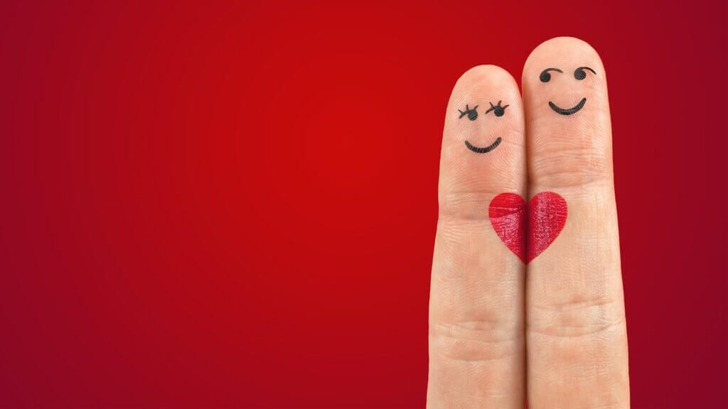 Red background image of two fingers with faces drawn on the tips and a read heart drawn across both