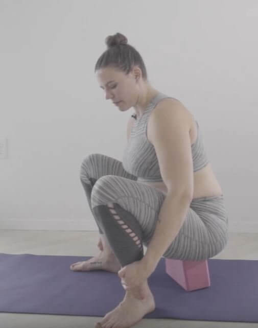 Feet apart she is in a squat knees bent tailbone resting on yoga block which is lain broad side down
