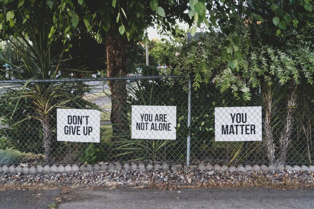 3 signs with black lettering on chain link fence read left to right don't give up, you are not alone, help is out there