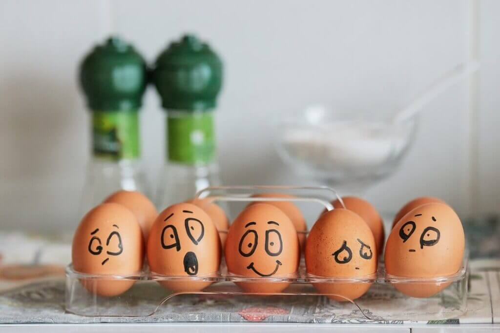 Brown eggs sitting in a clear tray on a countertop faces of mixed emotions are drawn on the shells