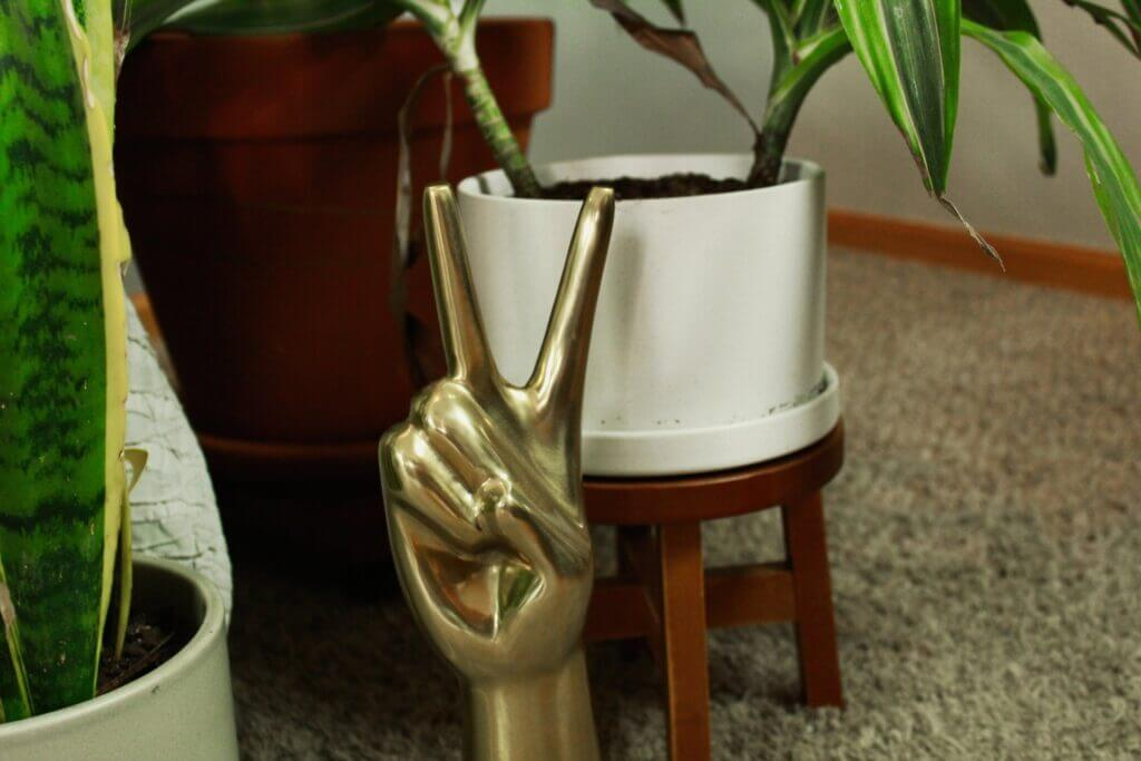 A gold hand statue making the peace sign with brown potted green plants on carpet in the background