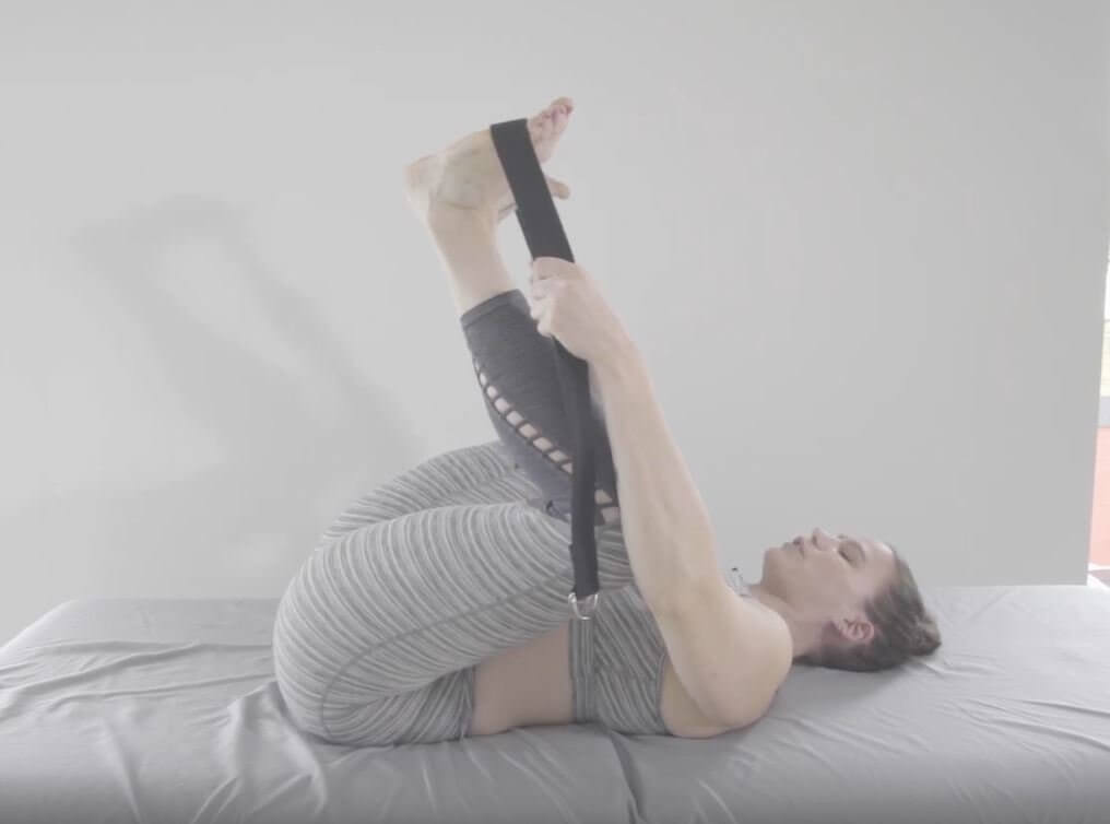 Laura on back knees apart and near chest arms hold yoga strap across feet pulling them near chest