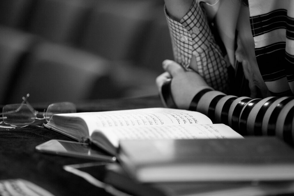 Black and white arms of person praying over open torah with dark strap wrapped up arm wrist to elbow