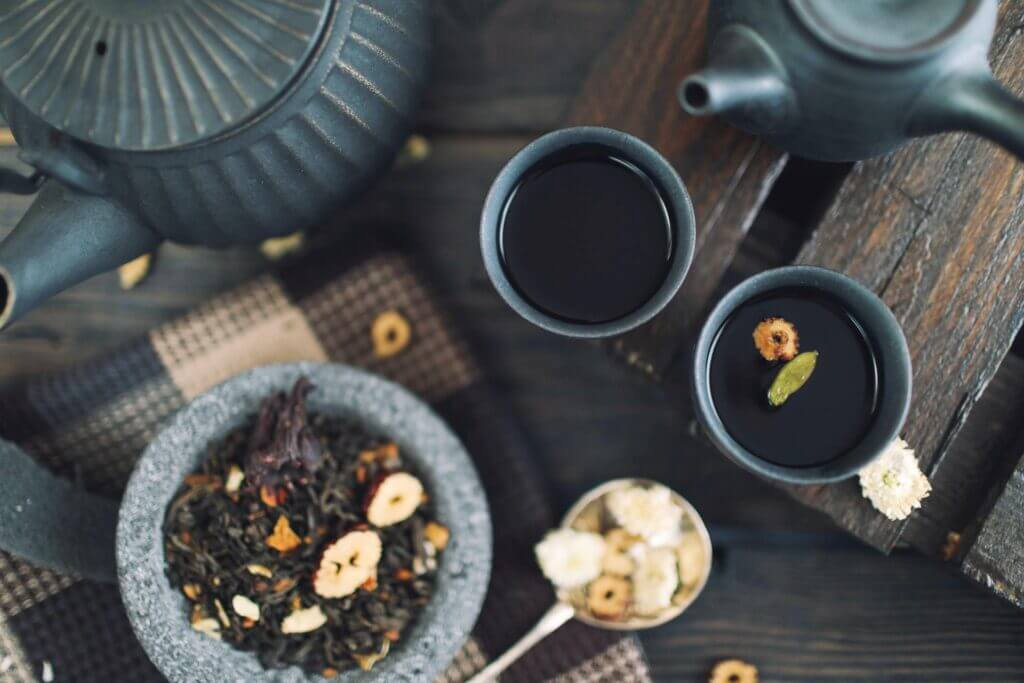 Dark gray tea kettles and cups sit on a tabletop with a bowl of herbs nearby and herbs in the liquid