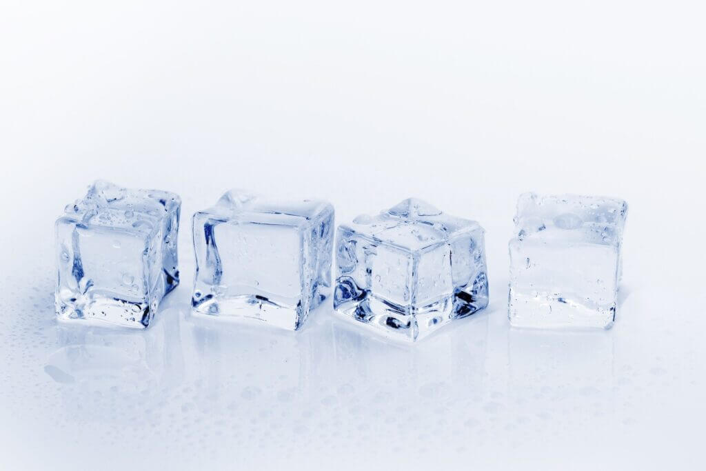 White background with four single square ice cubes sitting in a row across the image