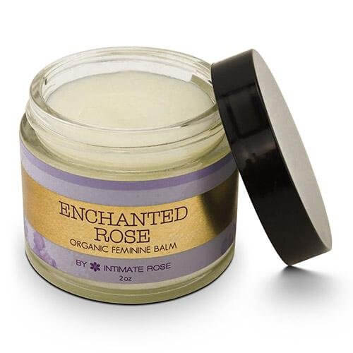 Round glass container black lid is open showing balm label read Enchanted Rose Organic Feminine Balm