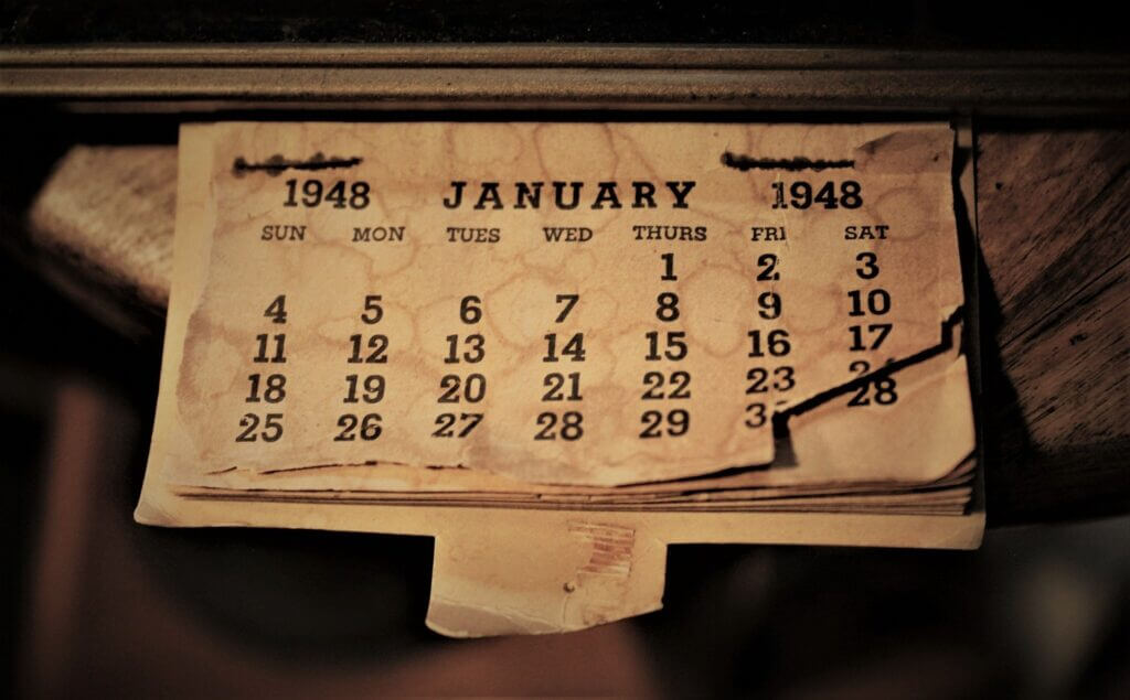 Sepia toned close up picture of an old curled paper calendar from the month of January in 1948