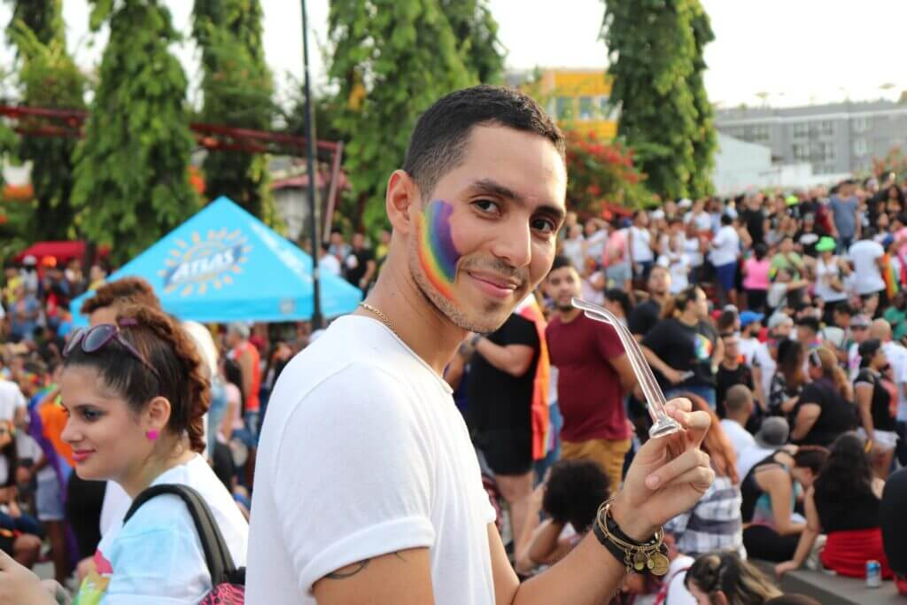 A man wearing a white tee shirt standing in a crowd at a gay rights march smiles at the camera as he holds his sunglasses, which have opaque white frames, in his hands. A rainbow is painted on his face.