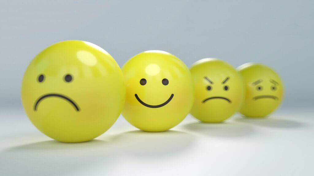 An image of round yellow emoji faces showing various emotions right to left: sad happy angry worried