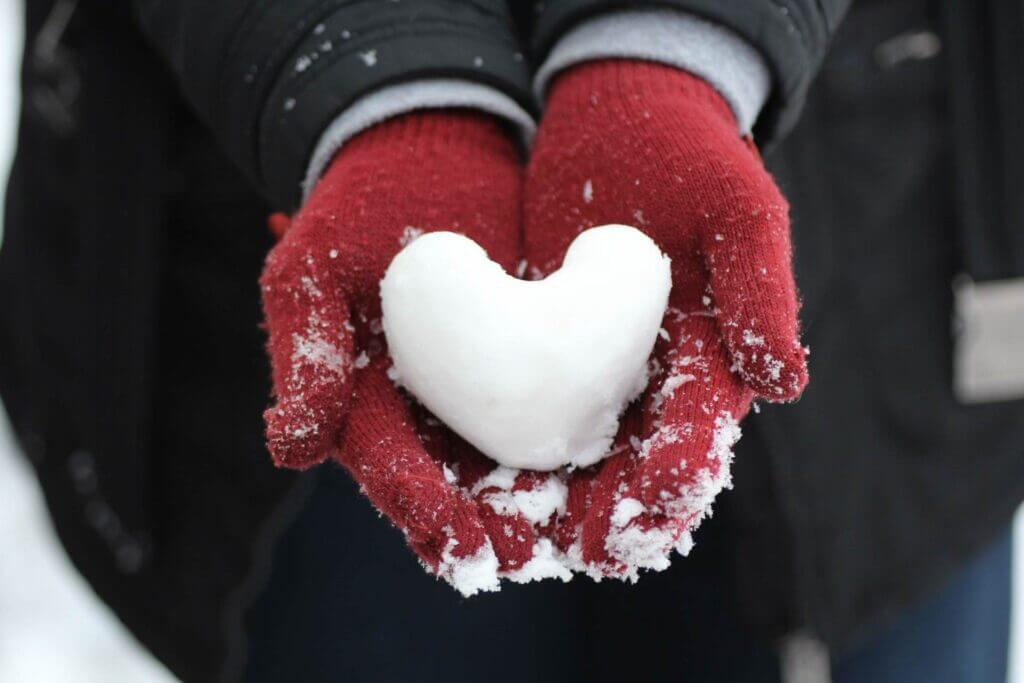 2 hands in red woolen mittens hold a packed snowball in the shape of a heart in their face up palms
