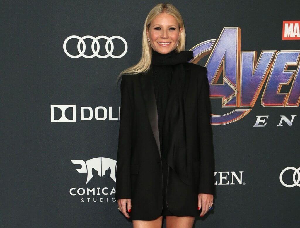 Image of actress Gwenyth Paltrow wearing black minidress standing in front of Marvel background