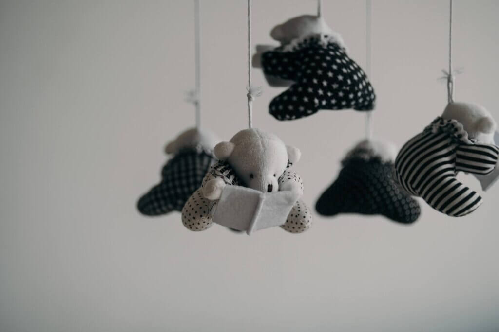 Black and white image of a small stuffed bear baby mobile the bears are reading small felt books