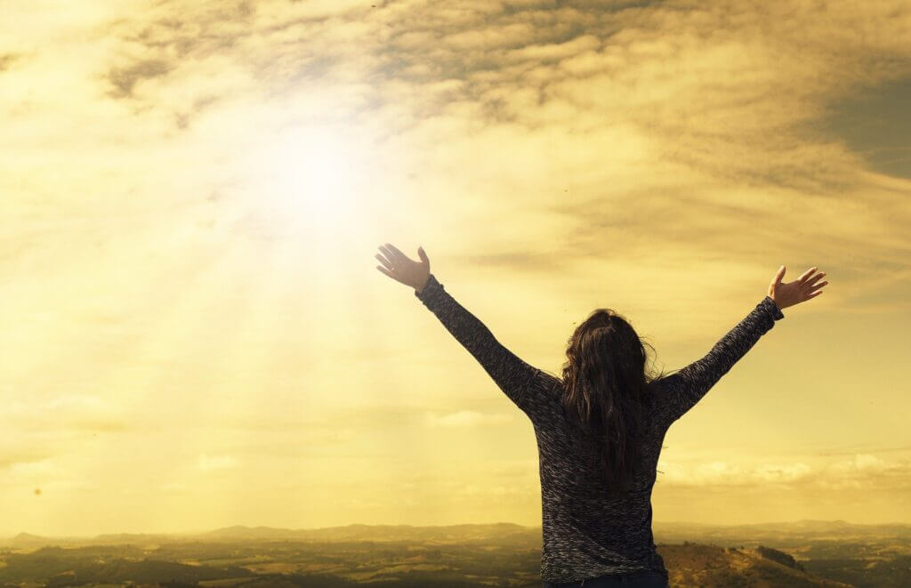woman from behind arms outstretched and raised up to shining sun clouds overlooking scenic hills