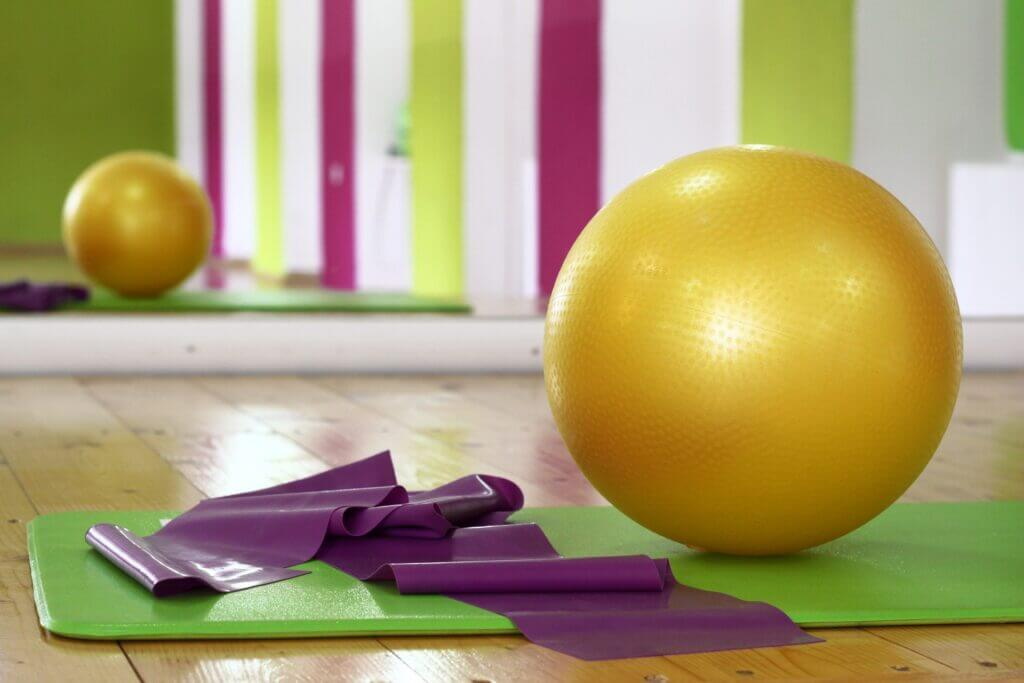 Yellow yoga ball right of purple mat on top of green mat on wooden floor in a gym in front of mirror