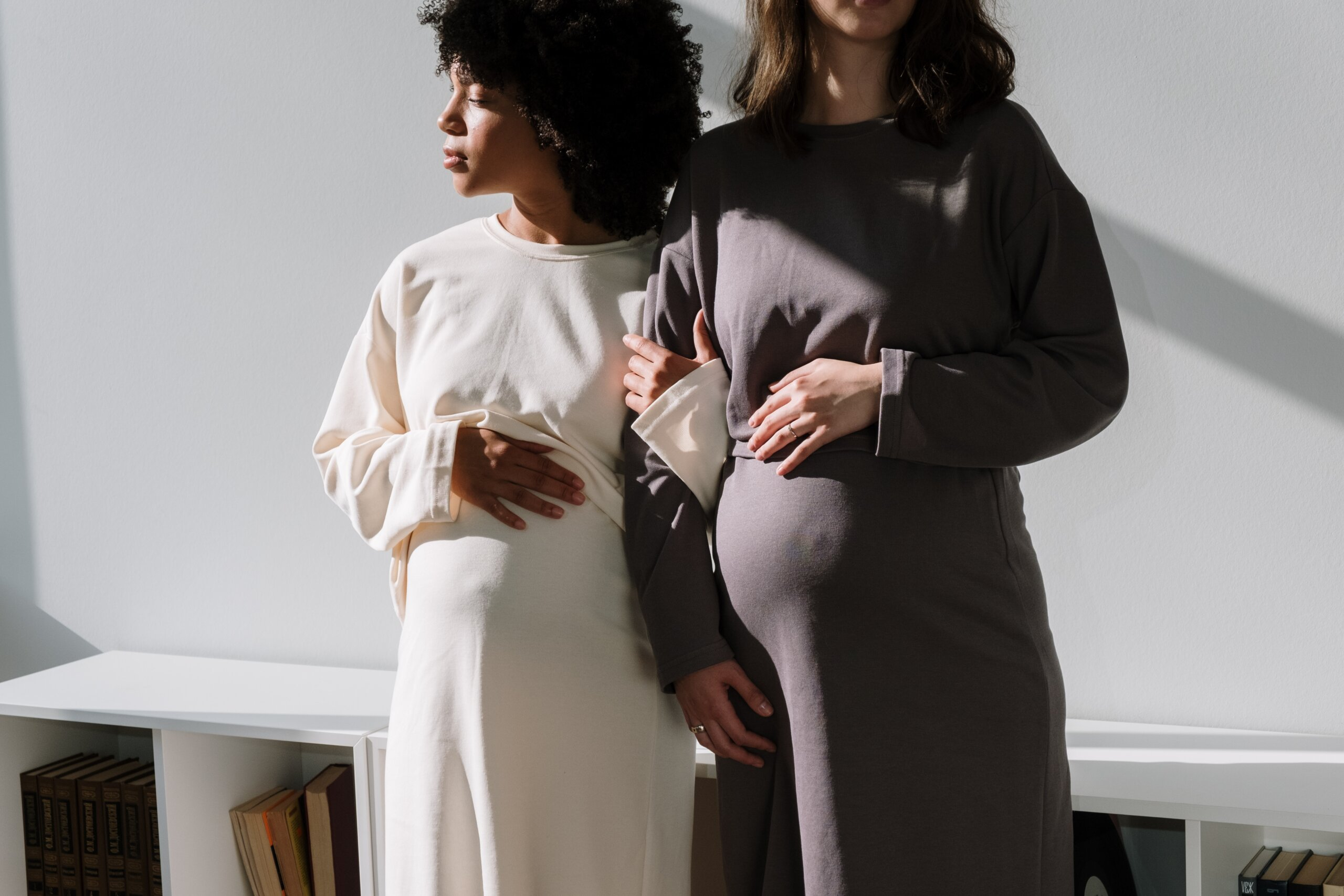 Pregnant woman in white dress with hand on her belly linking arms with pregnant woman in dark purple dress with hand on her baby bump
