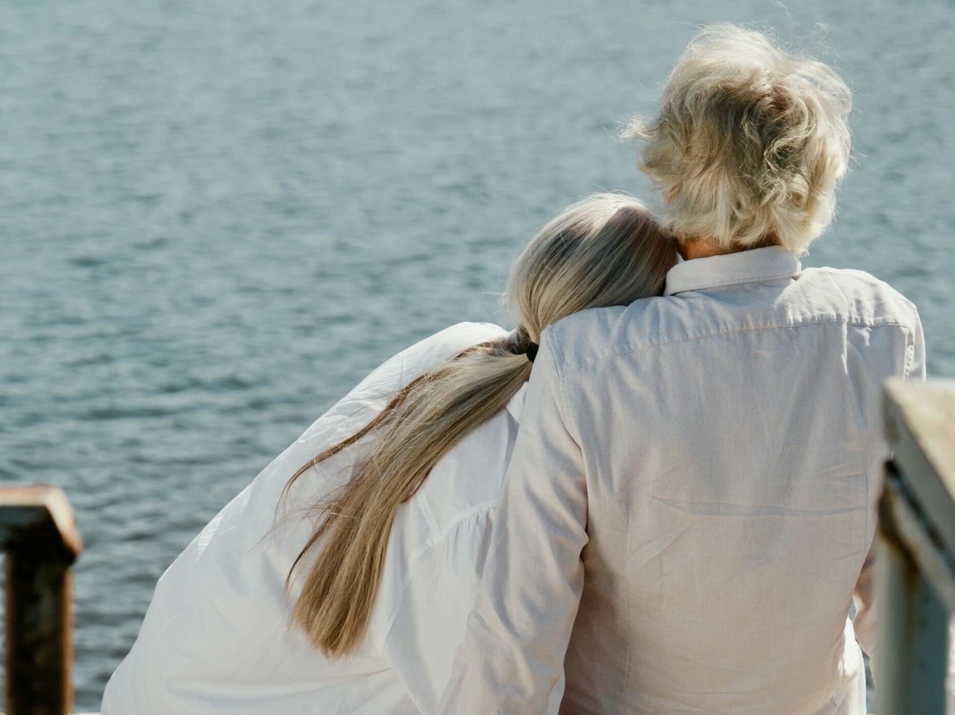 back view of older couple with grey hair embracing on a dock looking at the ocean