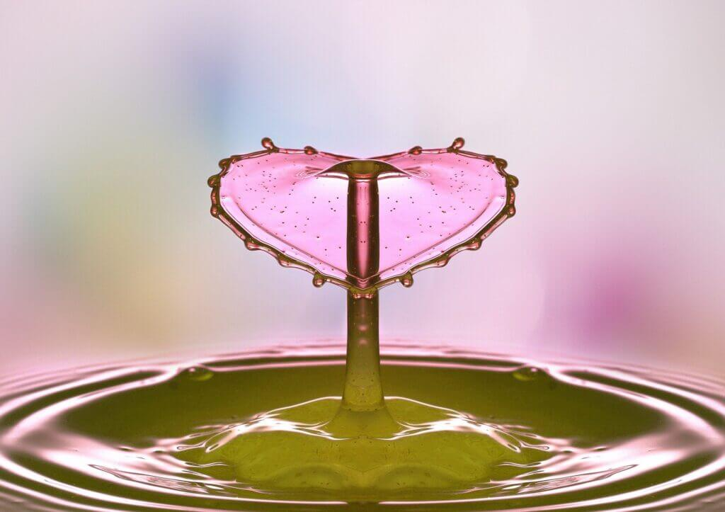 A droplet of water splashing in light pink water and the splash is in the shape of a pink heart