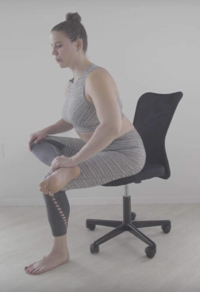 On office chair left foot on floor hand on right knee bent leg on top of knee chest leans forward