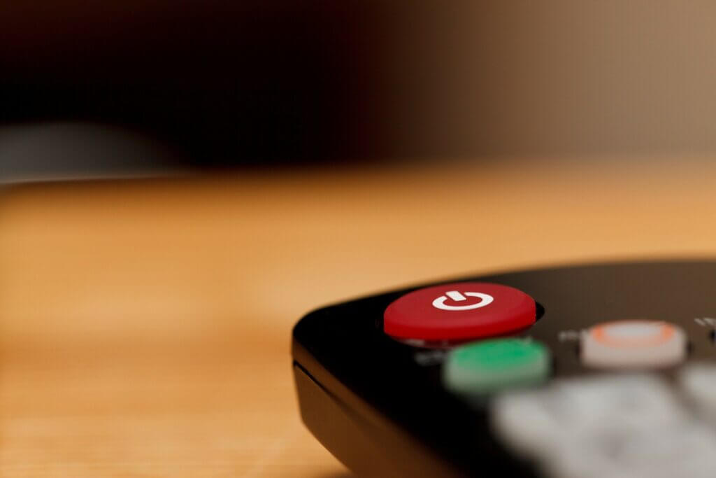 Close up image of the top corner of a black television remote controller's red power on off button
