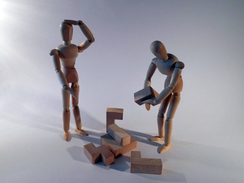 Wooden figurines pose confused and struggle to put together a multiple piece wooden 3d puzzle