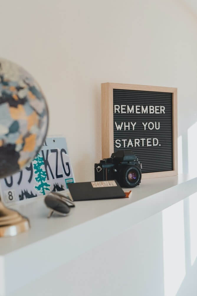 Photo white shelf with travel items on it black letterboard on right reads Remember why you started