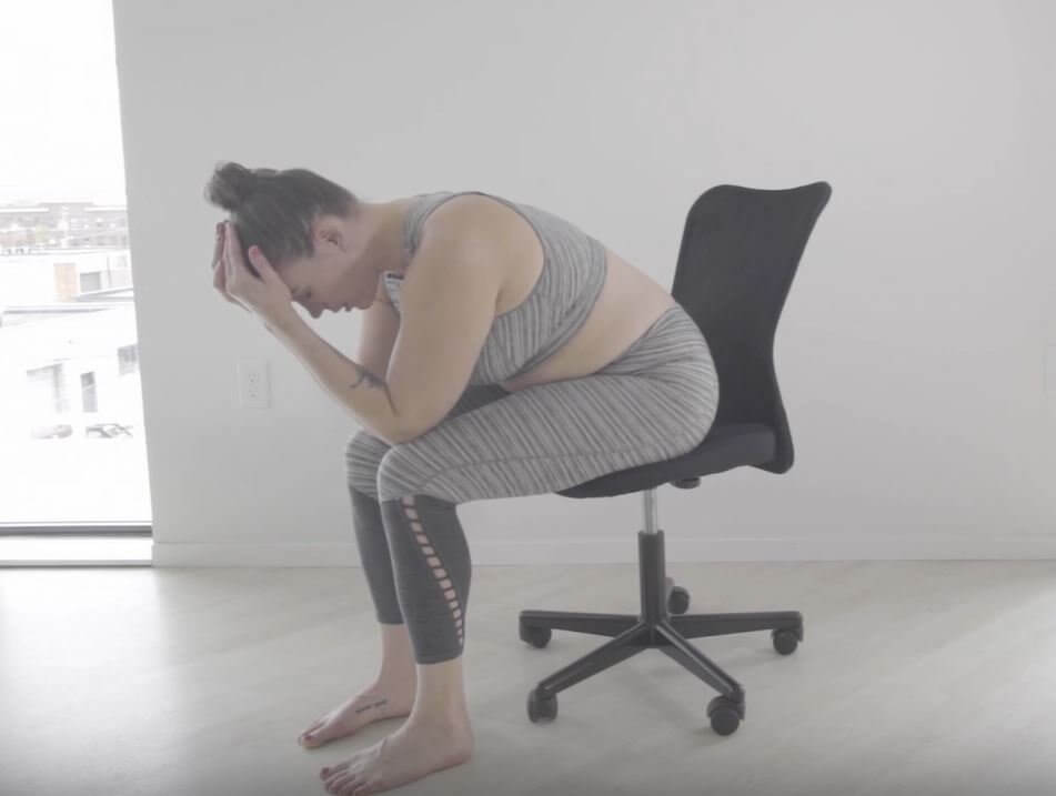 Laura sits on edge of black office chair feet on floor elbows rest on knees forehead rests in palms