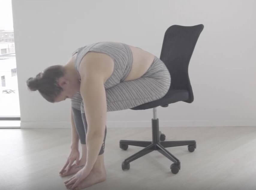 Sits on edge of black office chair feet on floor fingers touch floor next to feet chin between knees