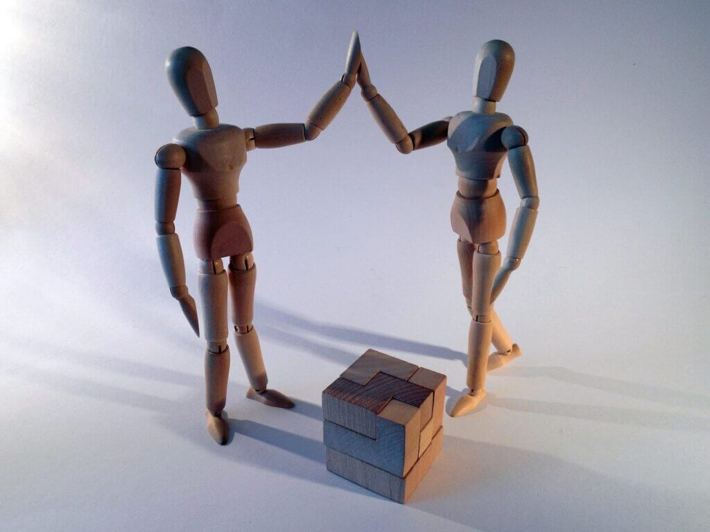 Wooden figurines high five proudly next to a solved multiple piece wooden 3d puzzle