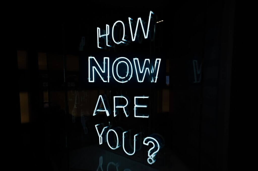 Black background with neon lights which spell out How Now Are You?