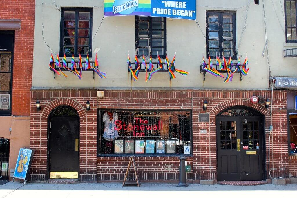 """A picture of the Stonewall Inn, a building that is brick on the first level and tan above that. There are many small rainbow flags flying on the second story of the building and above the flags is a banner that says """"Where Pride Began"""" with a Blue Moon logo."""