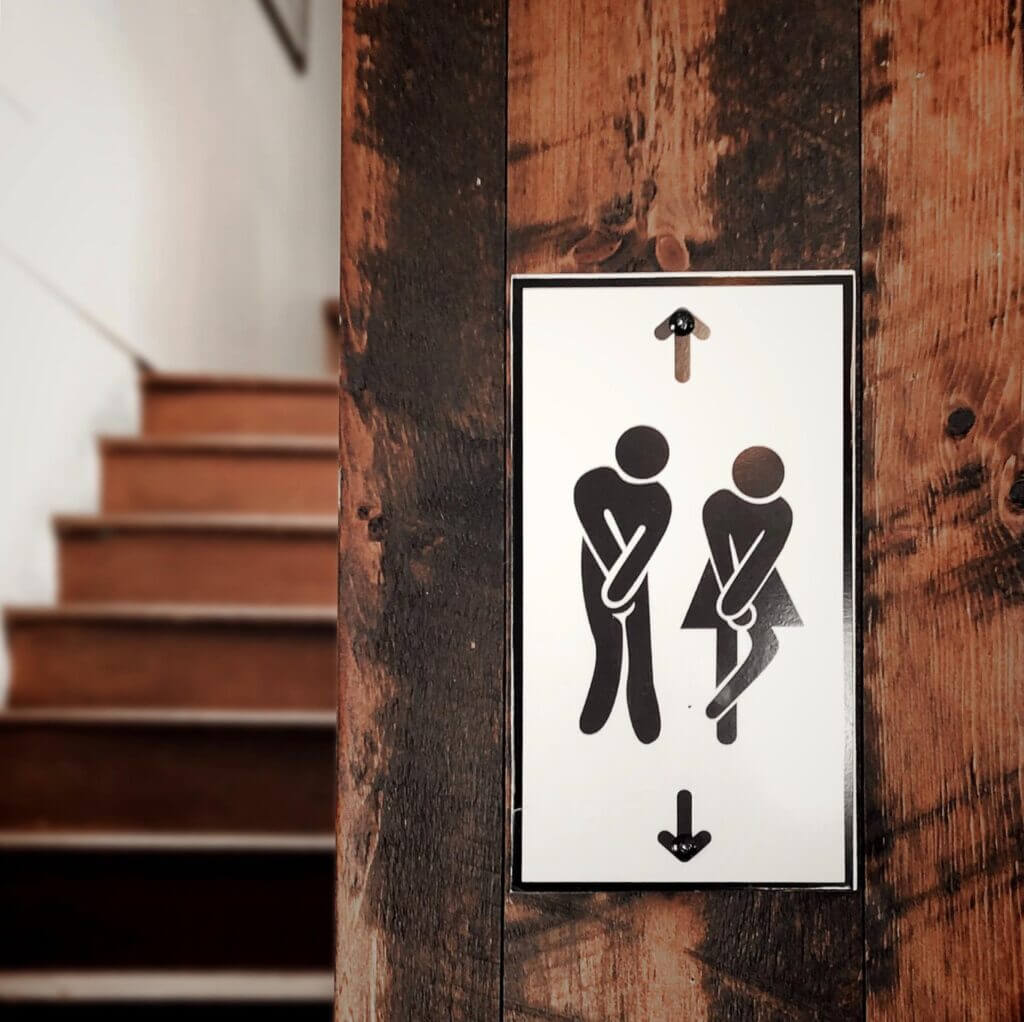 Black and white sign on wooden beam stairs in background black male female shapes hold crotch area