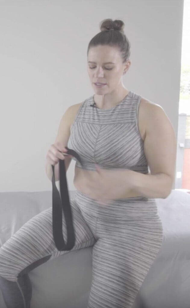 Laura holding black yoga strap in hands strap is in a loop shape tail hanging loose near left hand