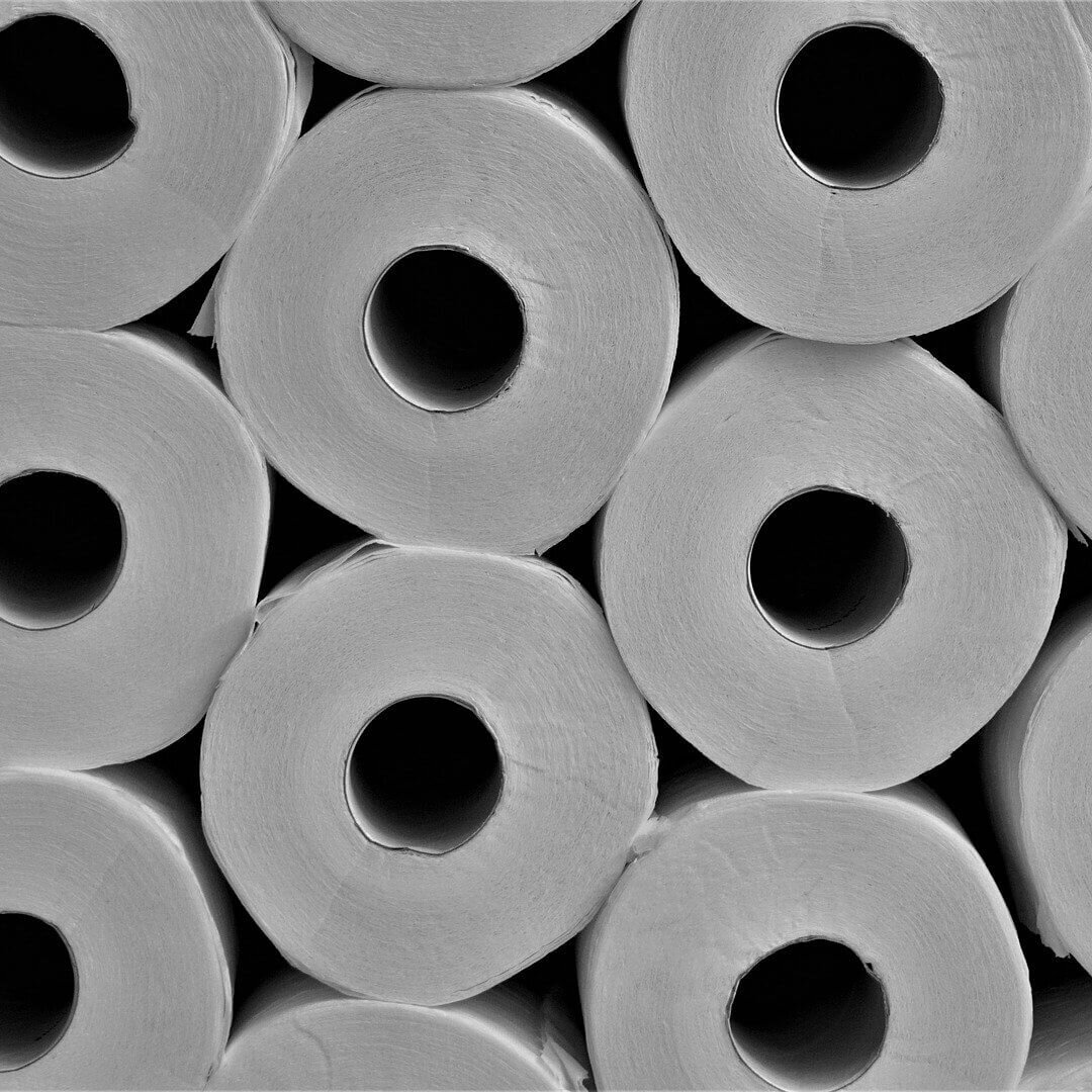 close up of stacked rolls of white toilet paper