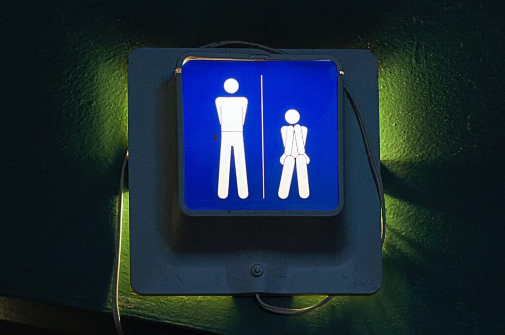 Image of bathroom sign showing one white figure standing and one sitting in front of greenish light