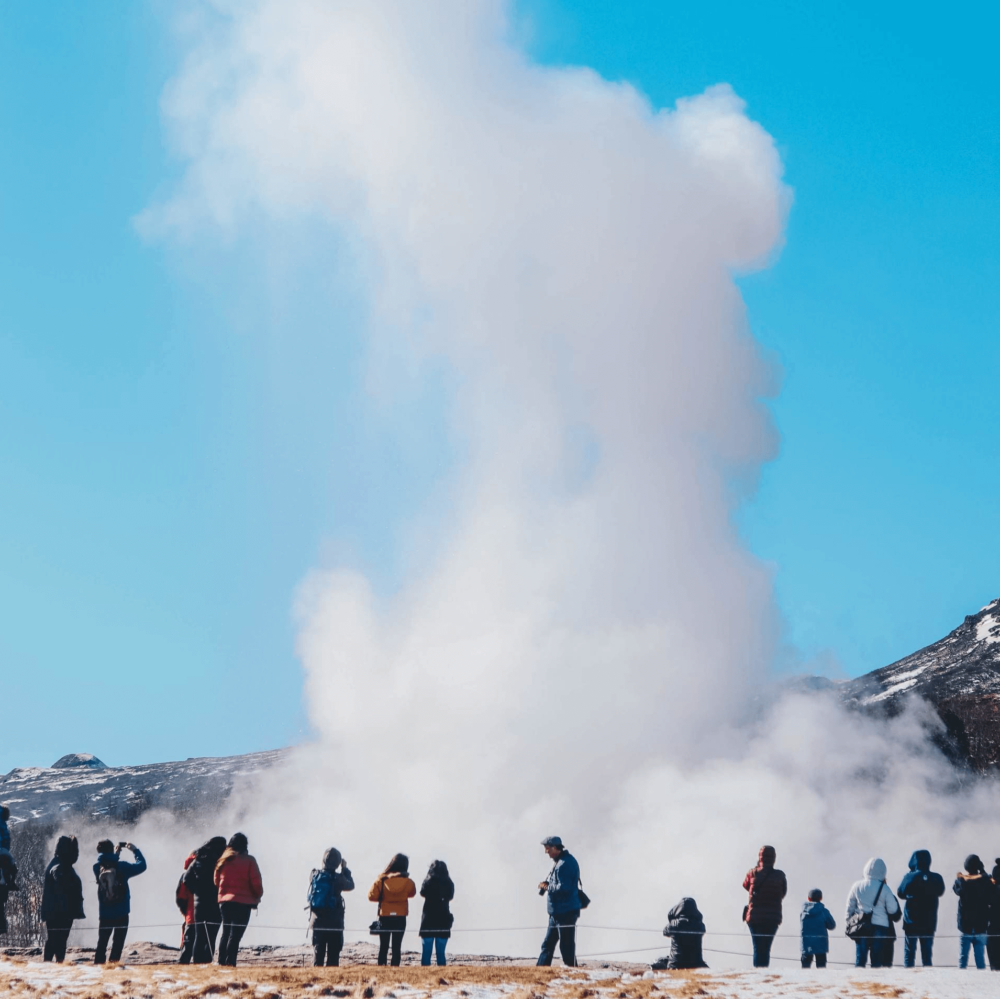 Steaming geyser with blue sky background and crowd of people watching in foreground