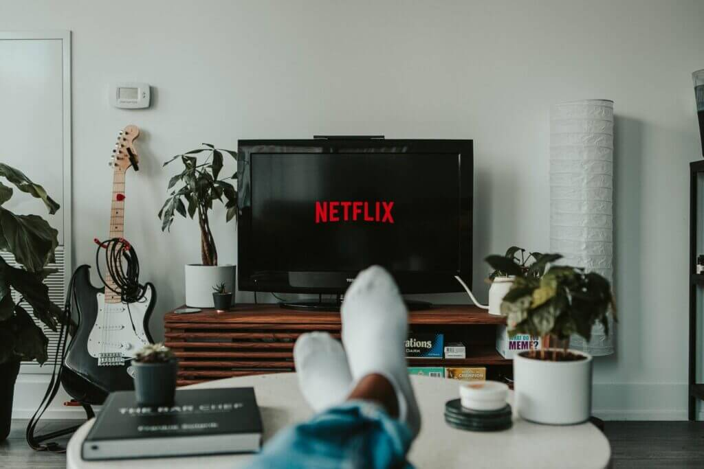 Flat screen tv displays Netflix logo on stand 2 feet are in foreground resting on white coffee table