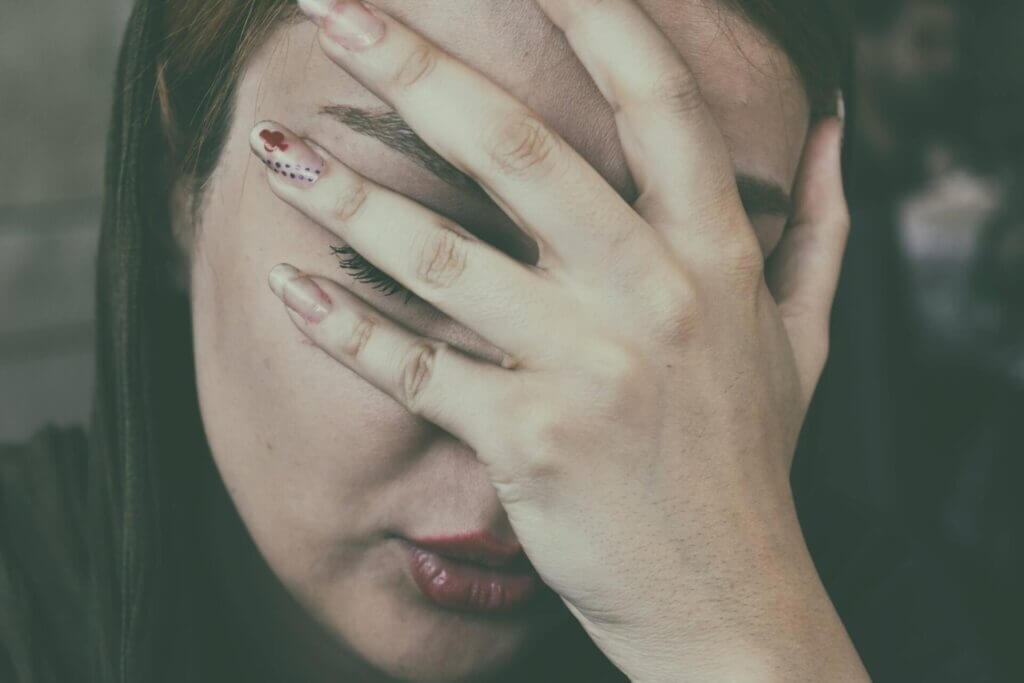 Close up of woman with dark hair her face is in her hand visibly upset red clover symbol on her nail