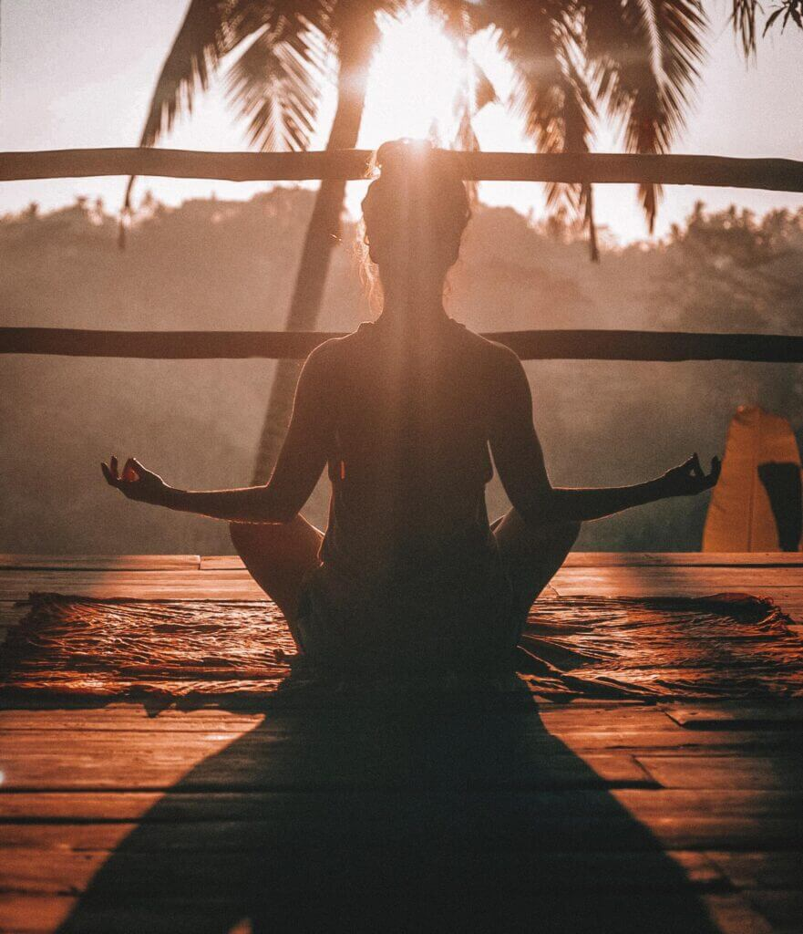 Woman sits in yoga pose on a mat on a wooden deck looking at a jungle in a tropical place at sunrise